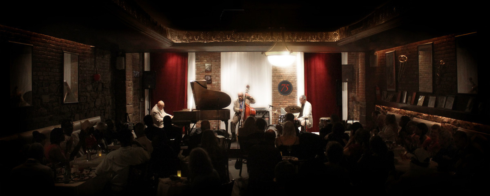 Photos of an evening performance at the club where three musicians on stage entertain the audience